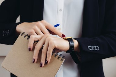 Woman in a business suit and dark red manicure holding a noteboo