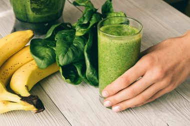 Female hand holding a glass of smoothie with spinach and banana