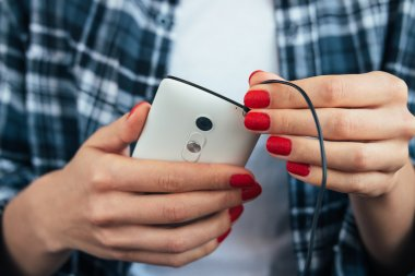 Girl in plaid shirt holding a smart phone in her hands with red