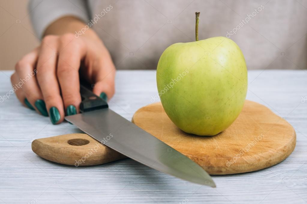 Mujer va a cortar manzana verde con un cuchillo de cocina — Foto de ...