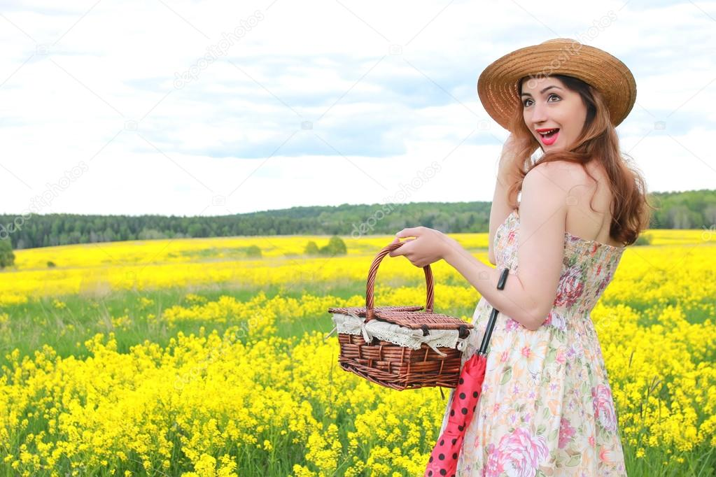 girl in a field of flowers with an umbrella and a hat