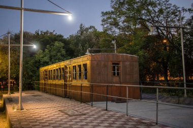 Old wooden carriages at night parked as an outdoor exhibition of railways in a park in the greek city of Kalamata. Outdoor railway museum in greece