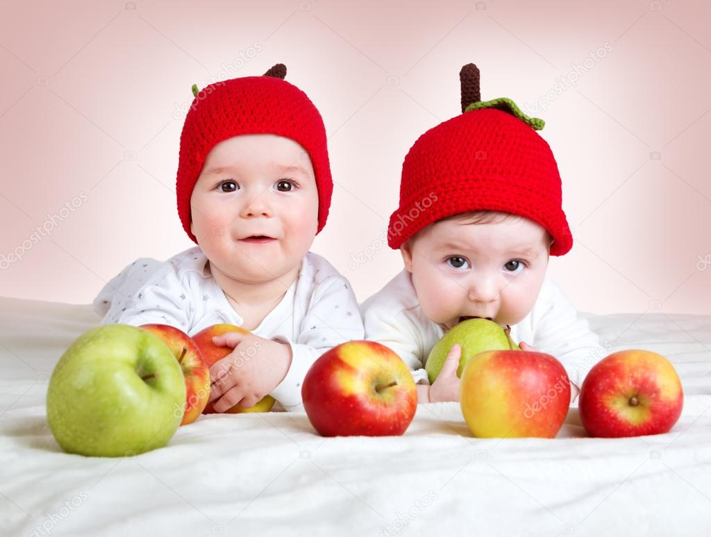 two cute babies lying in hats on soft blanket with apples — stock