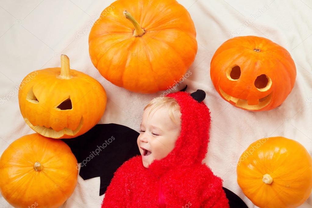 Dětské kostýmy čert s dýní. Dítě v halloween oblečení ležící na měkkou  bílou přikrývkou — Fotografie od ... 9d2c232eb8a