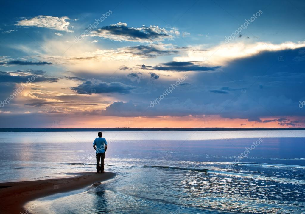 Alone man at sea in sunset