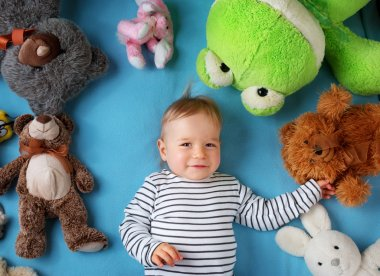 Happy one year old boy lying with many plush toys