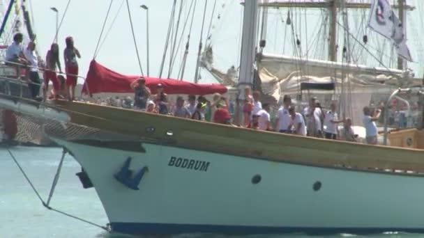 Plachetnice plachty a obrací s turisty na palubě lidé v přístavu