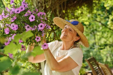 senior woman tends flowers