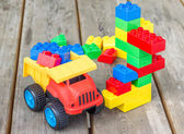 Photo Plastic building blocks and toy truck on wooden background