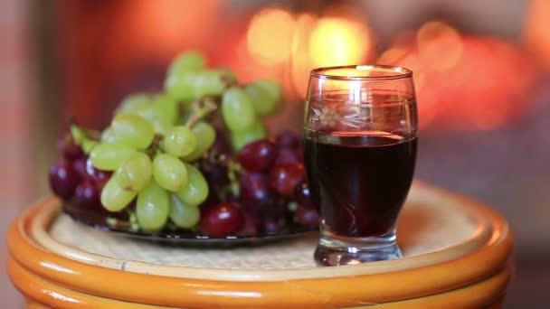 Deska s hrozny a sklenku vína na krb pozadí