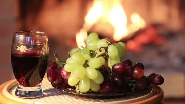 Teller mit Trauben und Glas Wein auf Kamin Hintergrund