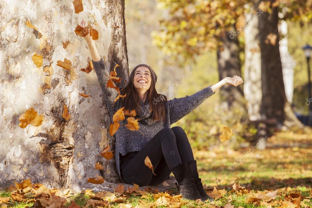 Woman drops up leaves in autumn park