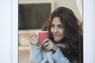 Young beautiful woman drinking coffee and looking out of the window