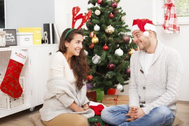 Couple exchanging gifts by Christmas Tree. Happy Couple in Santa