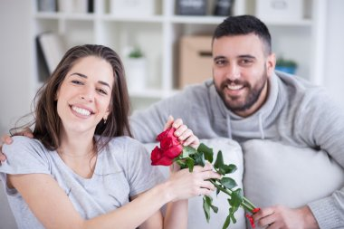 Young man giving a red rose to his girlfriend