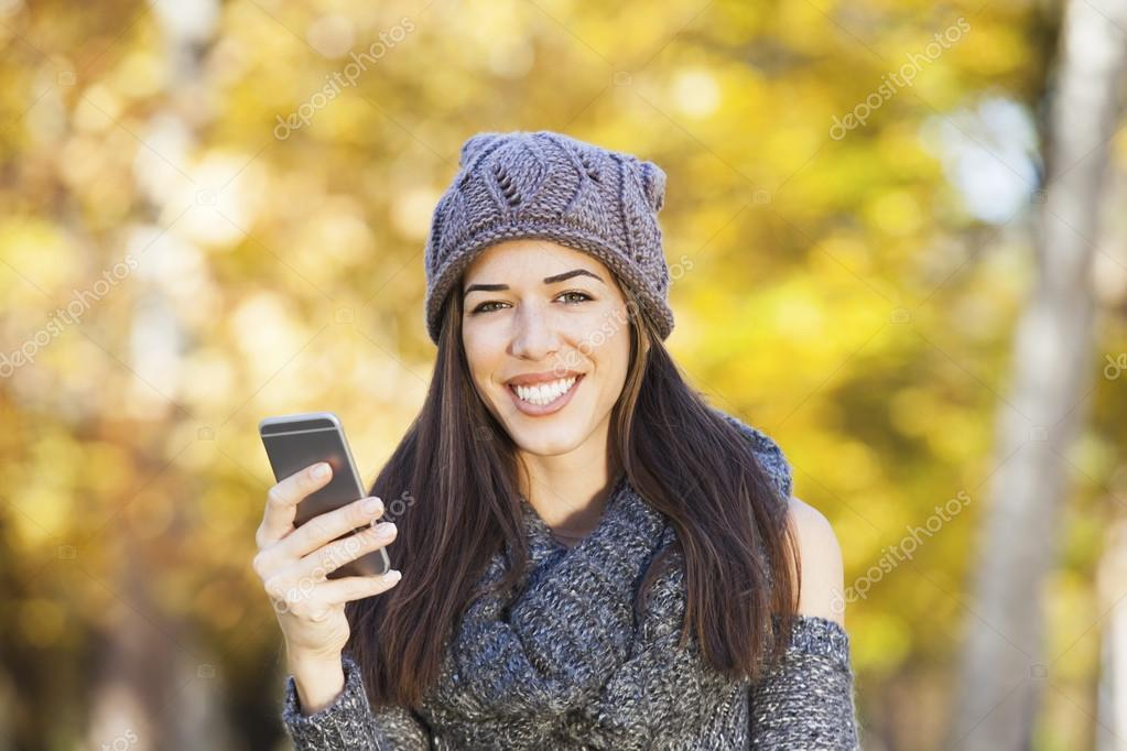 Beautiful woman walking in autumn park. Fall season. Woman talking on the phone