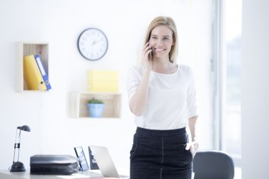 Businesswoman in office talking on phone