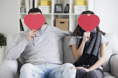 couple hiding faces behind paper hearts