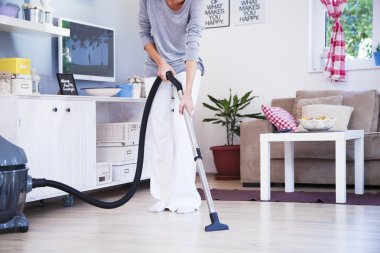 Close up of woman with legs vacuum cleaner cleaning floor at home