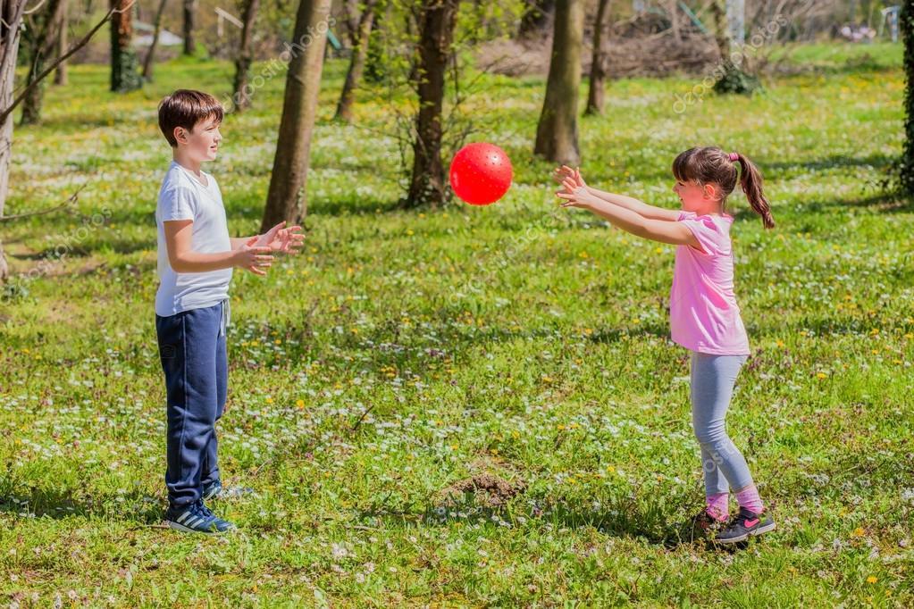 Niño Y Niña Jugando Con La Pelota En El Parque