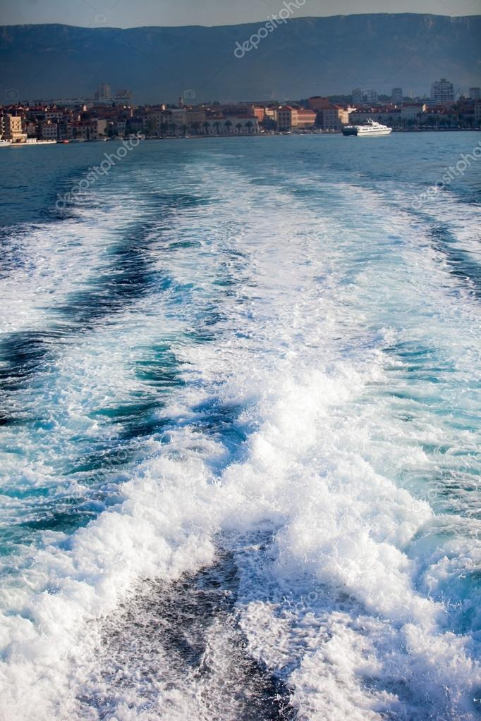 Trail on water surface behind of fast moving motor boat. Wake behind the ship