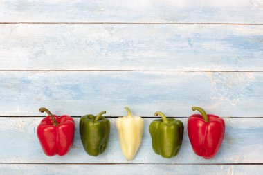 Colorful peppers on a blue wooden board, top view