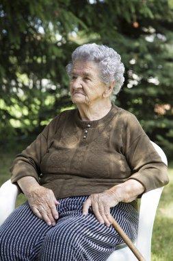 happy elderly woman sitting in garden