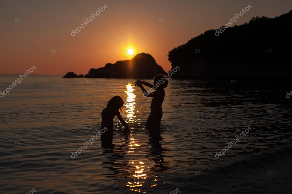 girls playing on the beach in sea sunset