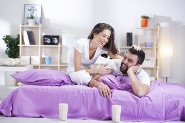 Happy young couple on bed sofa in ded room