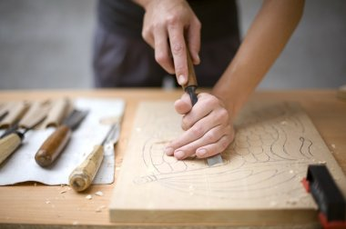 Wood carving on table with artist