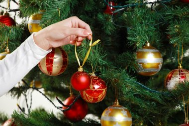 woman hands decorating christmas tree