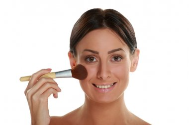 woman holding blush brush and applying make-up