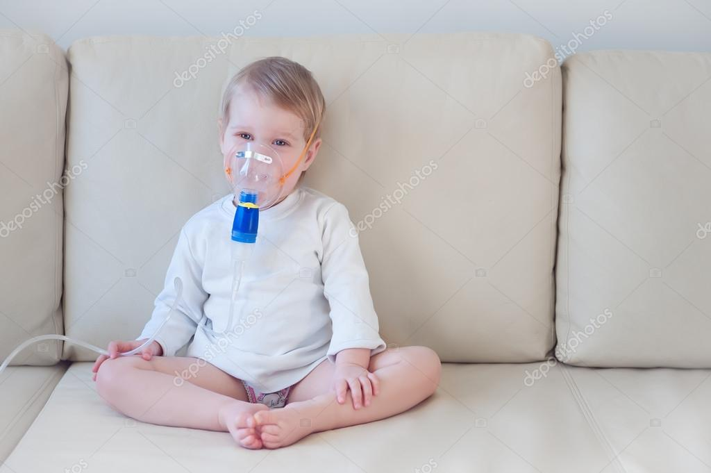 Baby girl making inhalation with mask on her face