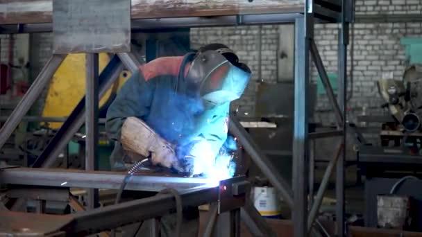 Professionelle Schwerindustrie Schweißer Workin, trägt Helm und beginnt mit dem Schweißen. Der Bau des Öls. Industrielle Fertigungsfabrik. Nahtschweißmetallurgie