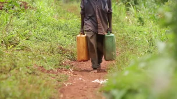 A man walking along a rural path with 2 water containers