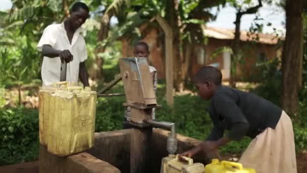 Africký kluk zaplňují žluté vody kontejnerů v dobře s jeho bratry a sestry
