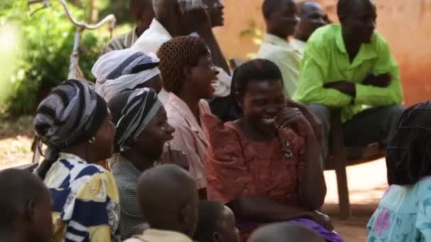 Africké ženy sedí a směje se na Společenství, zasedající v Masindi, Uganda, září 2013