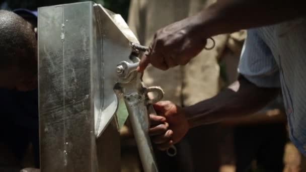 Two African men maintaining a water well in rural Masindi, Uganda, September 2013