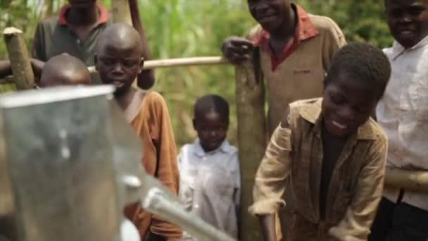 glückliche afrikanische kinder feiern die installation eines neuen wasserbrunnens in ihrem dorf, masindi, uganda, september 2013