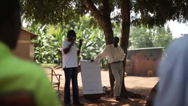 Afrikanerin unterrichtet ein Dorf über sanitäre Einrichtungen in der Gemeinde, masindi, uganda, September 2013