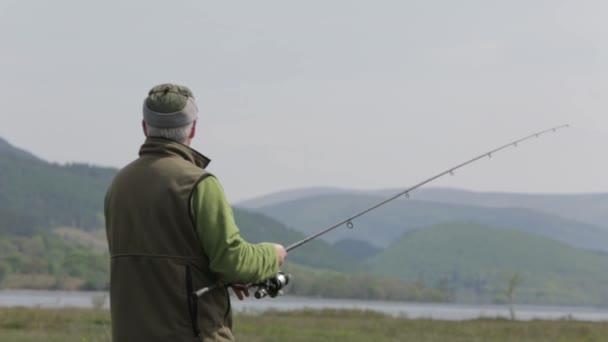 Rybář, obsazení je muškařského prutu v jezero ve Skotsku za slunečného dne, Fort William, Skotsko, července 2014