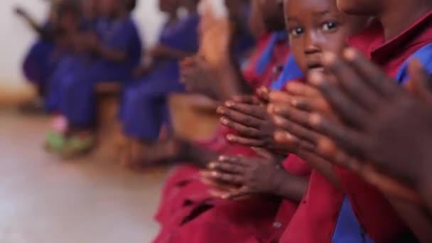 Malé africké školy děti zpívali a tleskali v uniformě, Keňa, březen 2013
