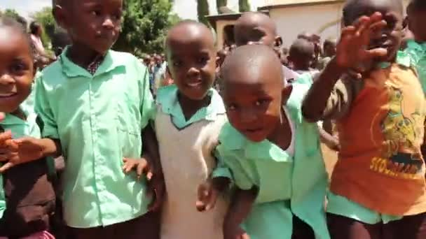 Group of young African children wave at camera smiling and happy, Kenya, March 2013