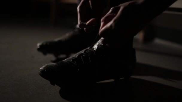 Footballer tying his laces getting ready for a match. Cinematic shot with lens flare