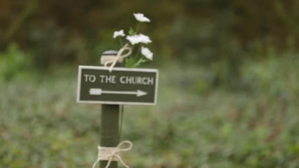 To the church sign, with flowers attached