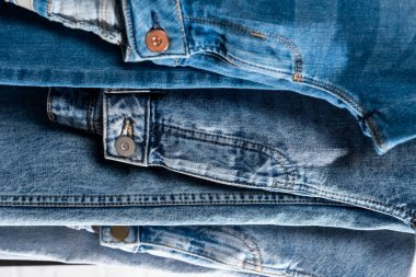 Stack of different blue jeans, close up view stock vector