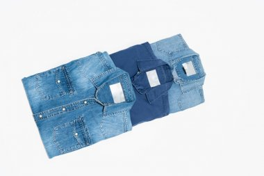 Top view of various blue denim shirts on white background stock vector