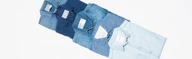 Diagonal row of different denim shirts on white background, top view, banner stock vector