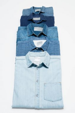 Vertical row of blue denim shirts on white background, top view stock vector