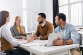 Lächelnde multikulturelle Geschäftsleute reden neben Laptop und Papieren